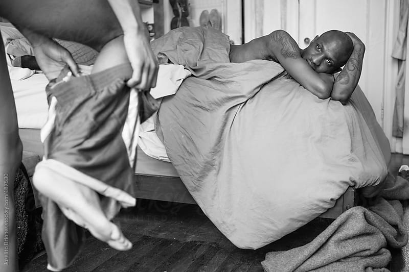 Black and White Photo of an Intimate Scene Between Two Gay Lovers in the Bedroom by Joselito Briones for Stocksy United