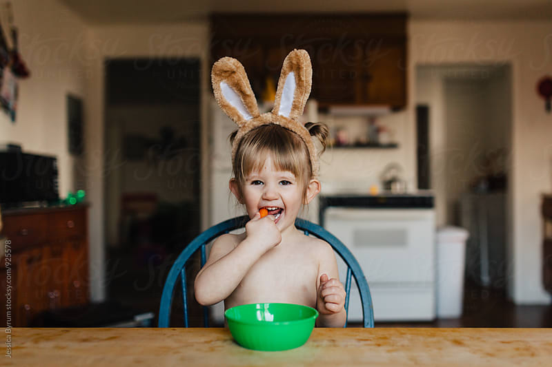 Toddler child wearing bunny ears and eating baby carrots at the kitchen table. by Jessica Byrum for Stocksy United