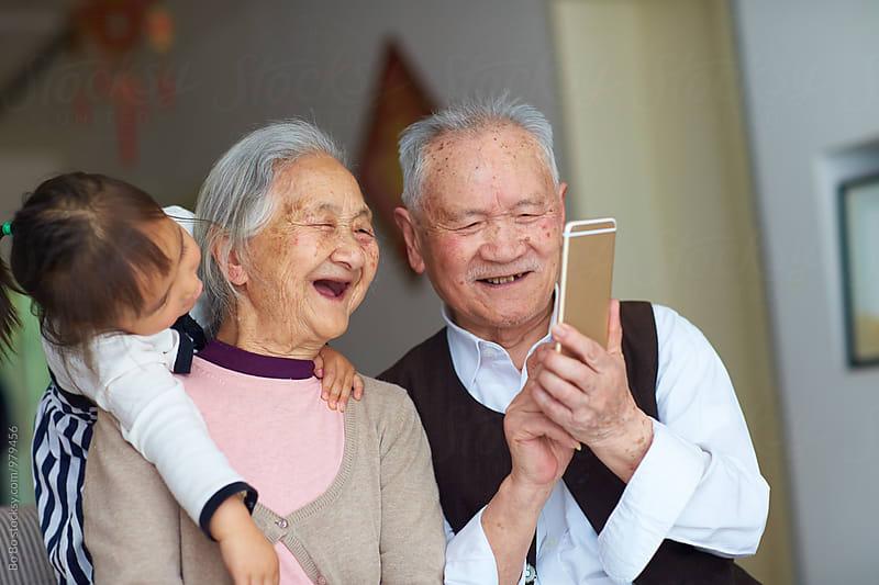 senior asian couple using smart phone indoor by Bo Bo for Stocksy United