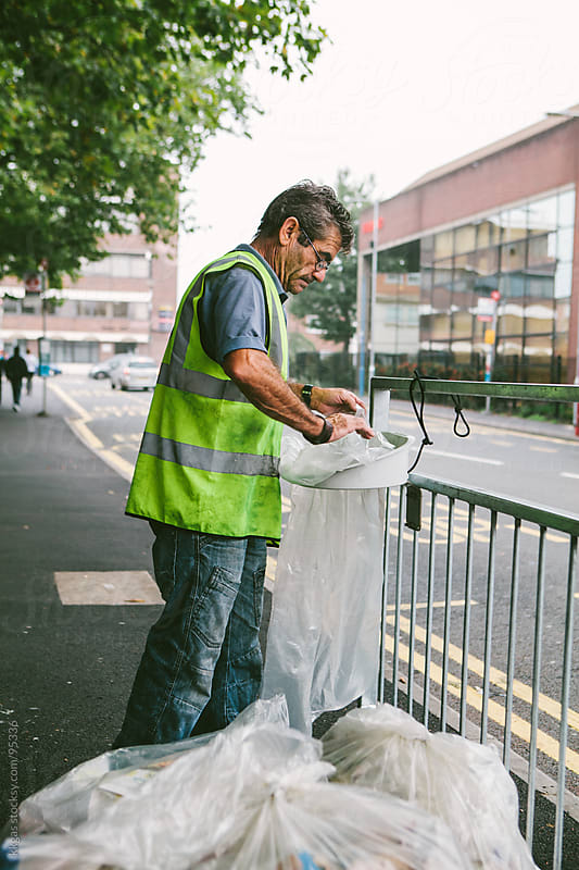Blue collar worker changing bin bags in the street. by kkgas for Stocksy United