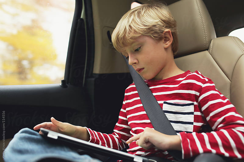 boy using an electronic device in the car by Kelly Knox for Stocksy United