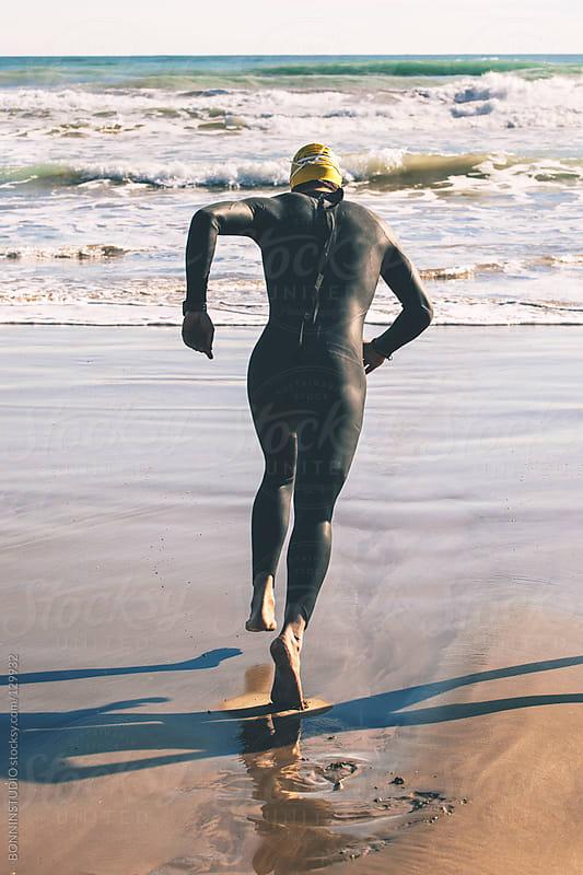 Triathlete running to the water on triathlon race. by BONNINSTUDIO for Stocksy United