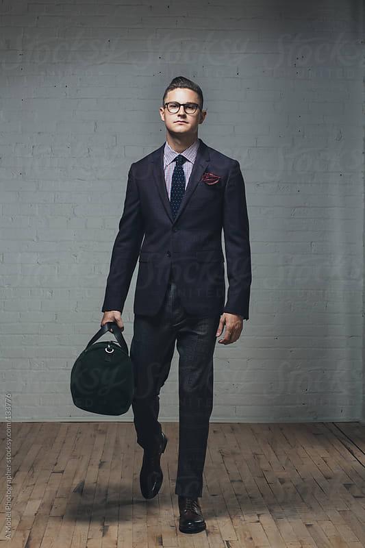 A man holding a duffel bag walking forward by Ania Boniecka for Stocksy United