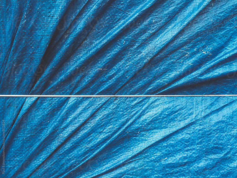 Close up of bound blue tarpaulin covering commercial fishing equipment by Paul Edmondson for Stocksy United