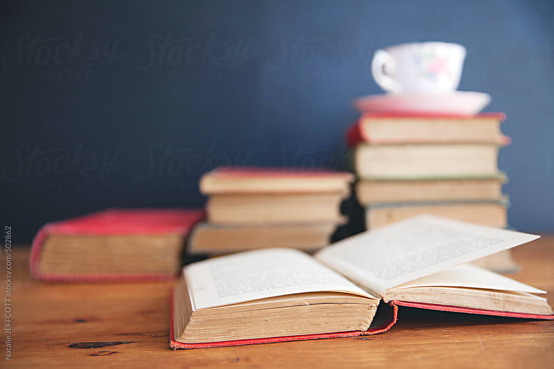 an open book on top of a pile of books with cup by Natalie JEFFCOTT for Stocksy United