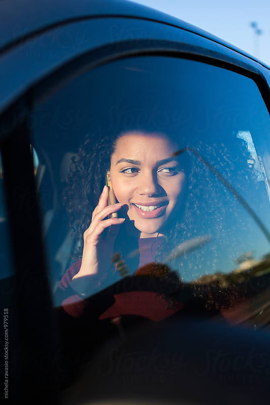 Attractive woman sitting in the car calling with cell  by michela ravasio for Stocksy United