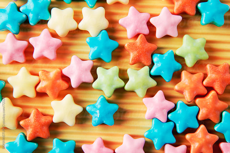 Sugar candy stars on orange background. by BONNINSTUDIO for Stocksy United