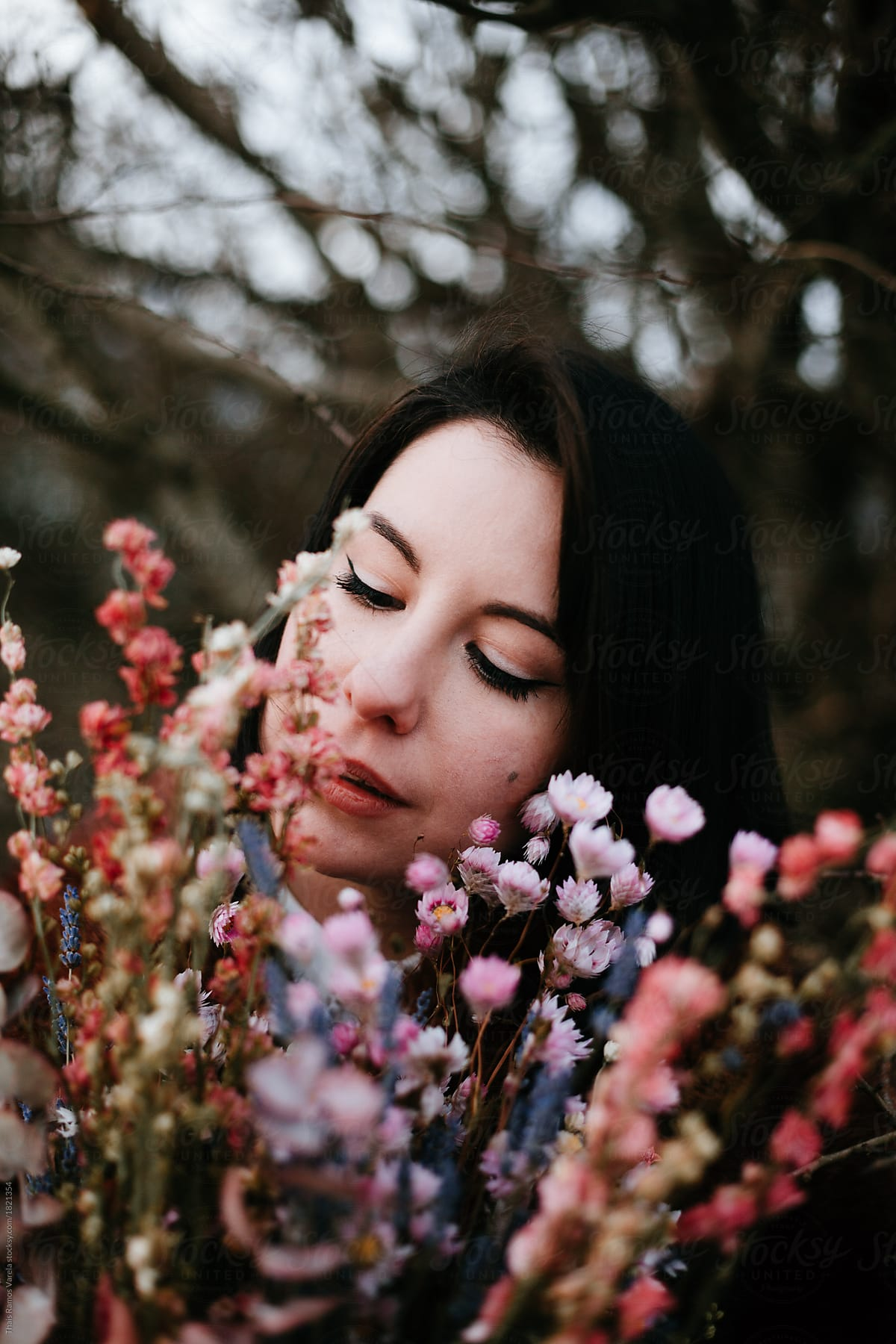 Portrait Of A Beautiful Woman Smelling The Flowers Stocksy United