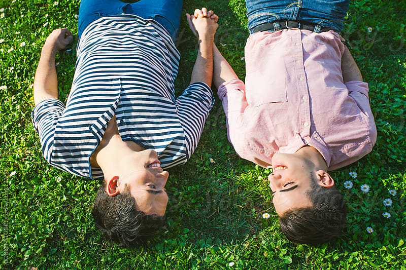 Smiling gay couple relaxing on the grass of a park. by BONNINSTUDIO for Stocksy United