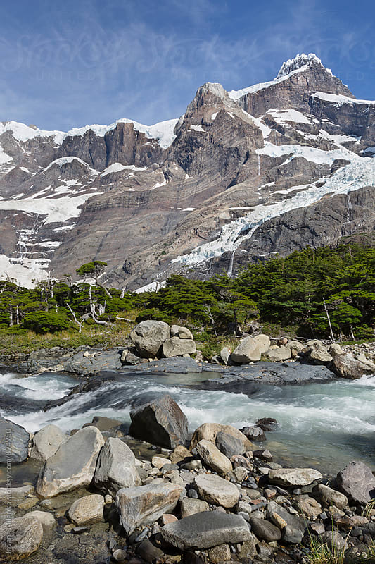 Glacier river flowing trough the forest under  the mountains covered in glaciers  by Jovana Milanko for Stocksy United
