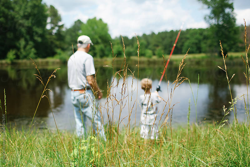 boy and his grandfather fishing at a pond by Kelly Knox for Stocksy United