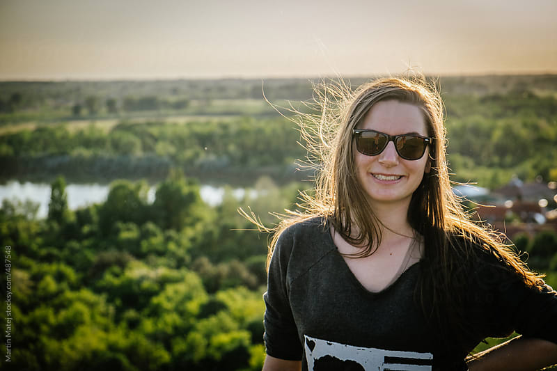 Girl with sunglasses standing on top of a hill during sunset by Martin Matej for Stocksy United