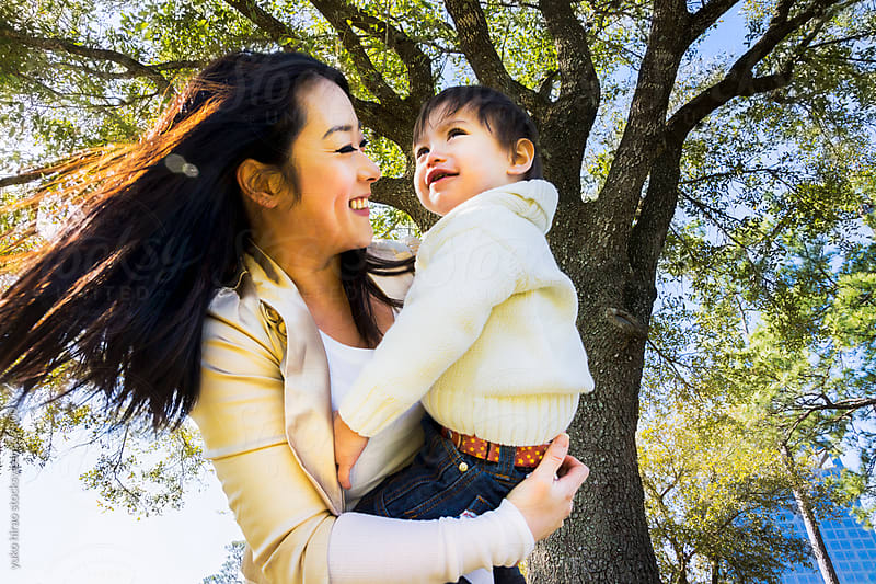Happy Asian mother, holding little boy outdoors by yuko hirao for Stocksy United