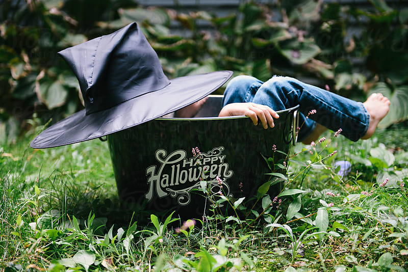 child in witch hat costume hides in a Halloween decoration by Tara Romasanta for Stocksy United