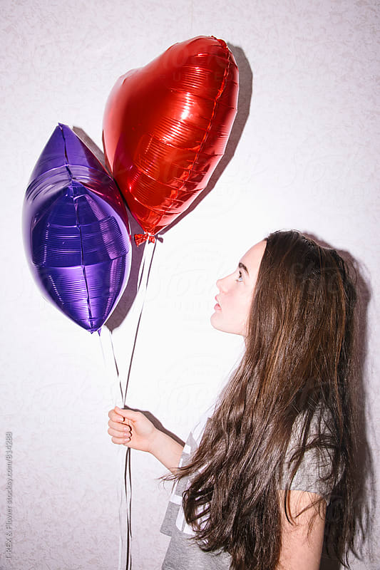 Side view of young woman looking at two balloons by Danil Nevsky for Stocksy United