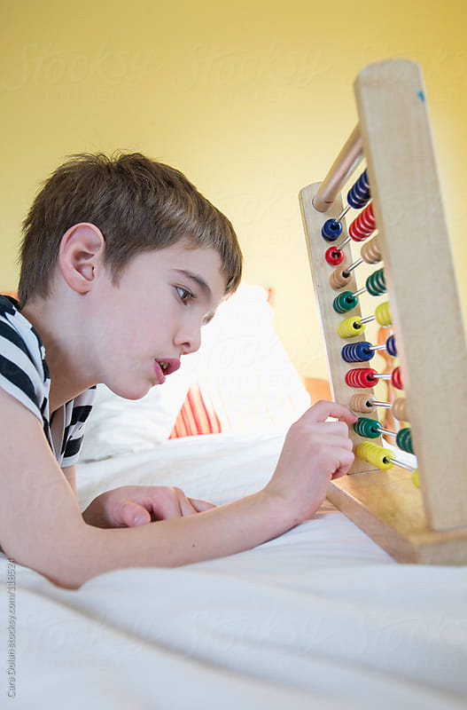 Child plays and learns with an abacus at home by Cara Dolan for Stocksy United