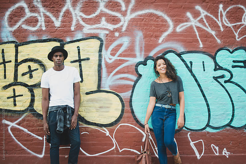 Couple standing in front of graffiti wall by Lauren Naefe for Stocksy United