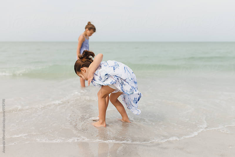 Two young girls looking for shells in the shallow ocean by Amanda Worrall for Stocksy United