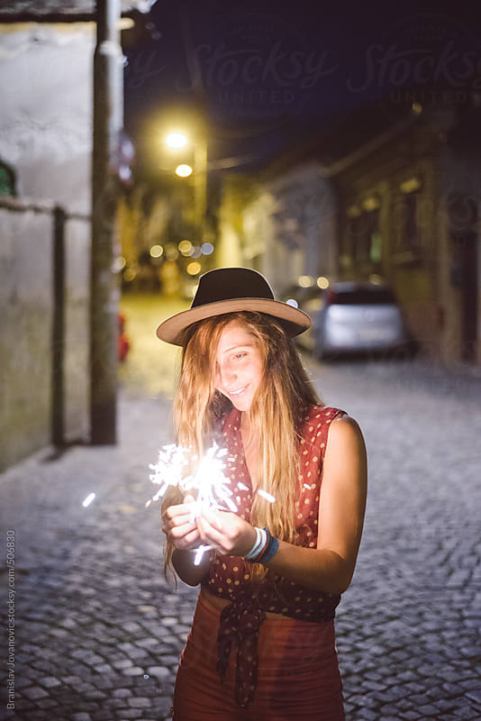 Beautiful young woman holding sparklers by Branislav Jovanović for Stocksy United