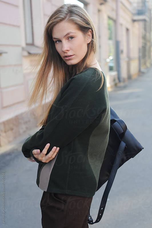 Young woman with a backpack looking at camera by Lyuba Burakova for Stocksy United