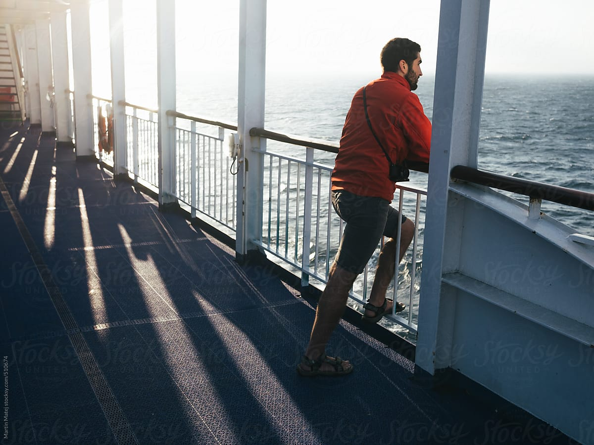 man leaning over railing on ferry and looking far away stocksy united