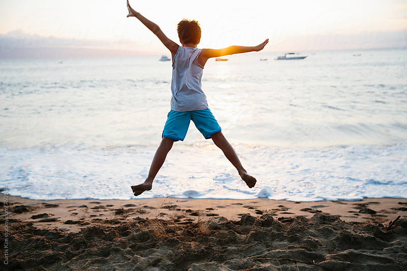 Boy jumping off of sand into the sea by Curtis Kim for Stocksy United