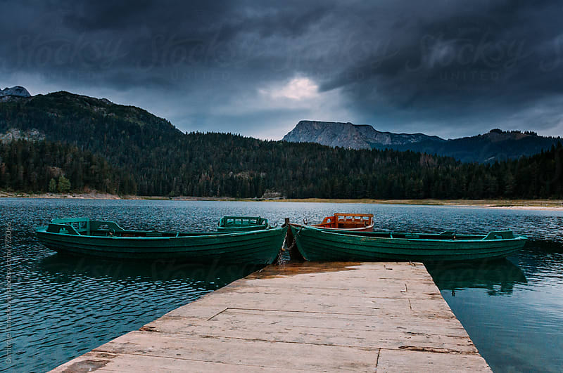 Tied boats on the mountain lake in the evening by Dimitrije Tanaskovic for Stocksy United