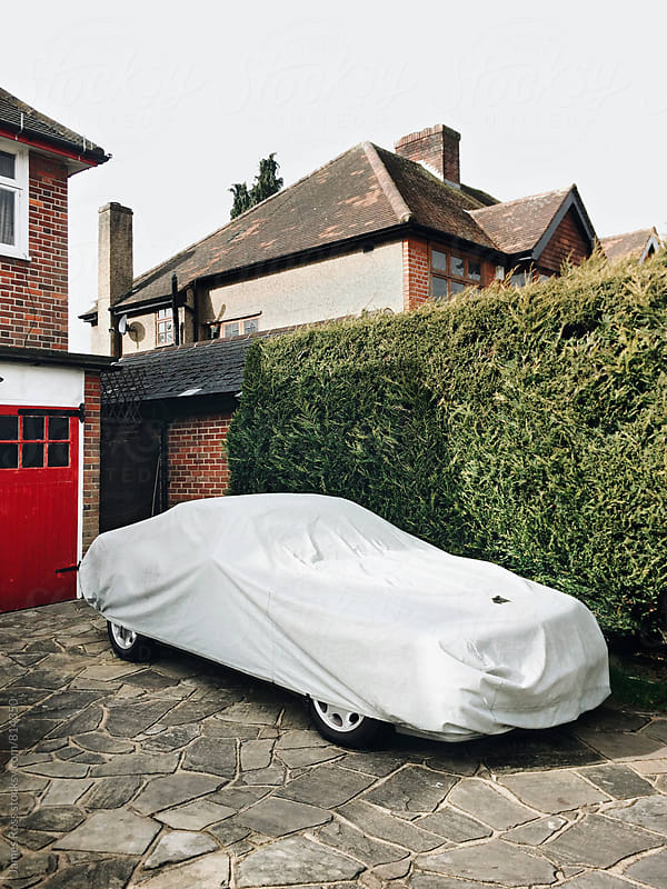 A covered car parked in a friveway by James Ross for Stocksy United