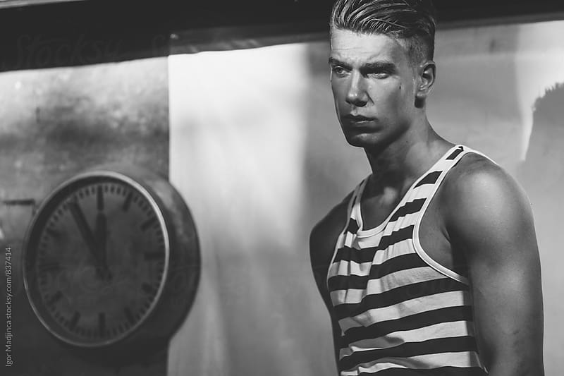 time, clock, past , handsome fashionable young man in a striped shirt  by Igor Madjinca for Stocksy United
