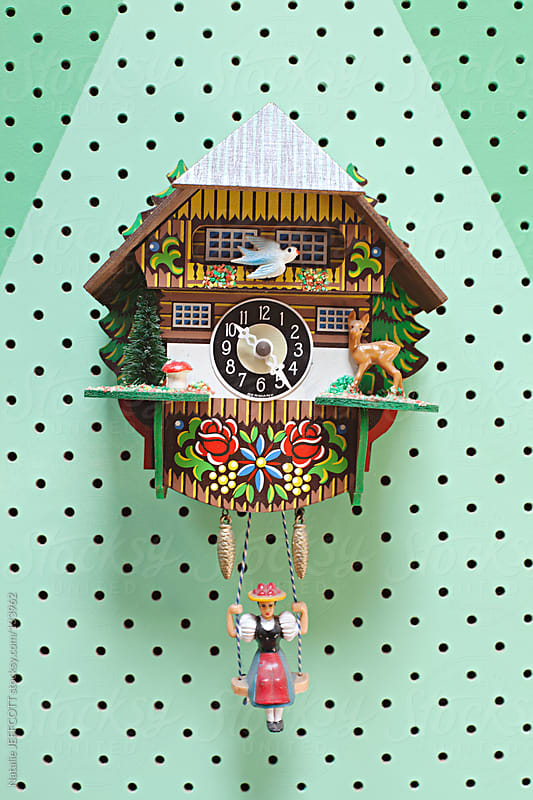 Colourful vintage cuckoo clock on green wall by Natalie JEFFCOTT for Stocksy United