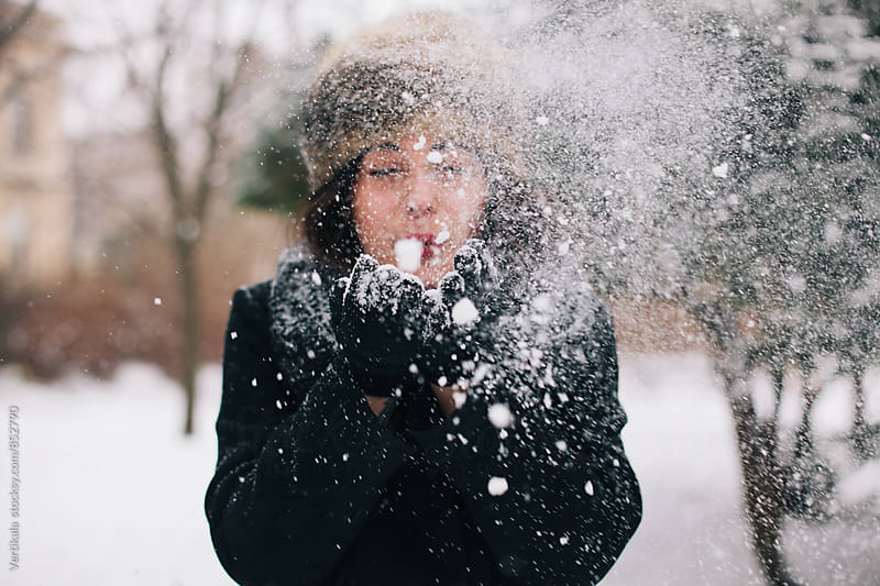 Woman blowing snow from her hands by Marija Mandic for Stocksy United