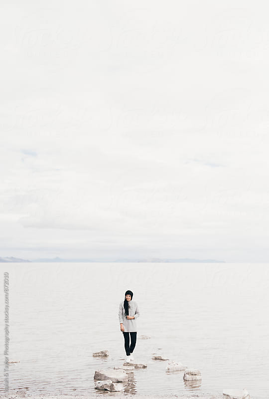 Woman standing near desert lake by Isaiah & Taylor Photography for Stocksy United