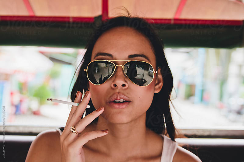 Girl smoking in Tuk Tuk by Jesse Morrow for Stocksy United