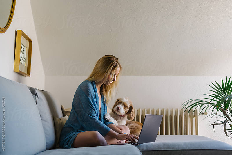 Beautiful Woman Playing with Her Dog at Home While Using a Laptop by VICTOR TORRES for Stocksy United