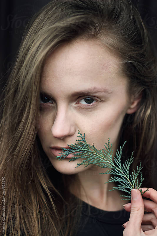 Girl holding plant next to her face by Hamza Kulenović for Stocksy United