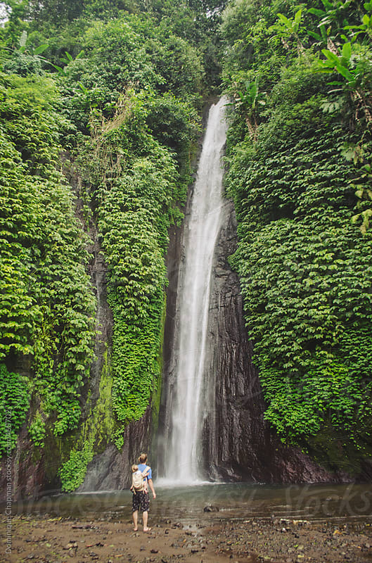 Man and child standing in front of Munduk Waterfall by Dominique Chapman for Stocksy United