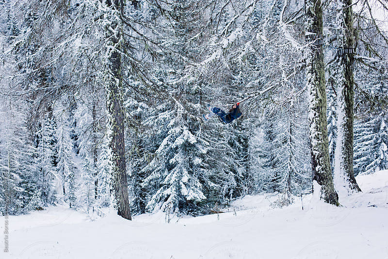 Girl looks like flying on the swing in the snowy Winter forest by Beatrix Boros for Stocksy United