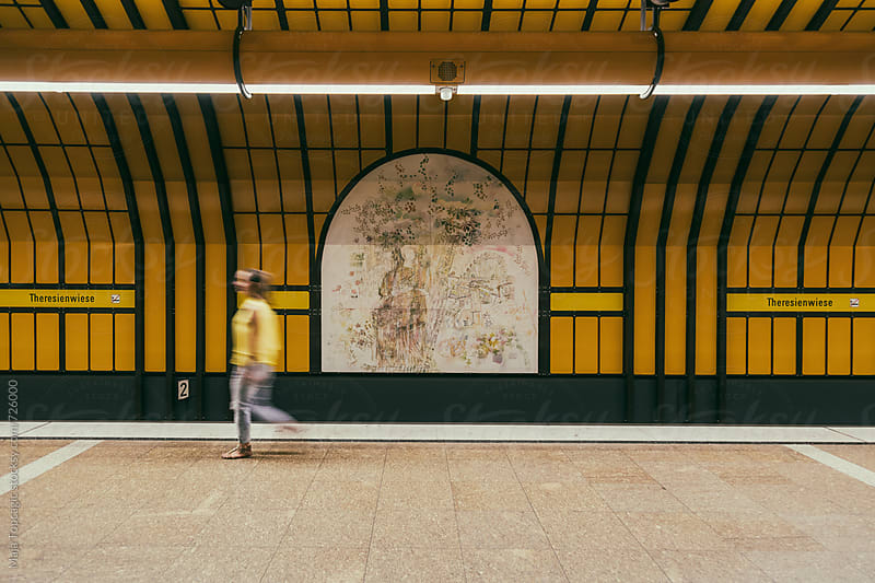 Young beautiful woman in yellow shirt walking in subway station by Maja Topcagic for Stocksy United