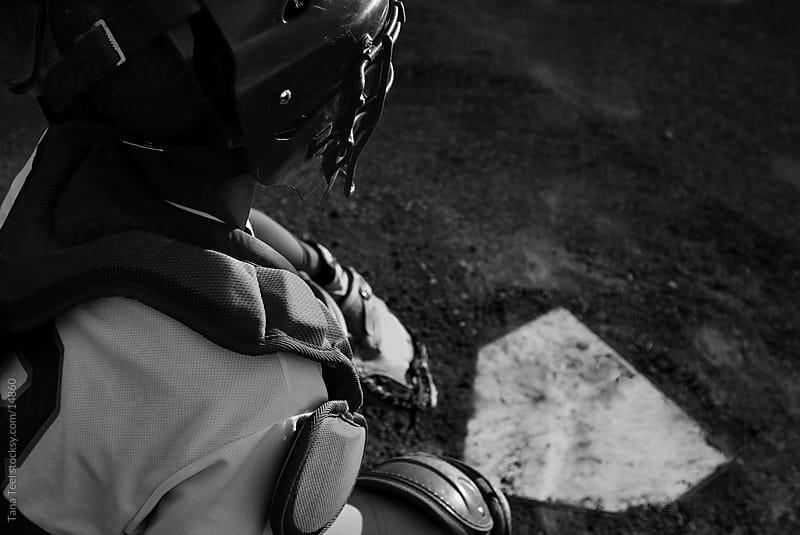The catcher behind homeplate.  by Tana Teel for Stocksy United