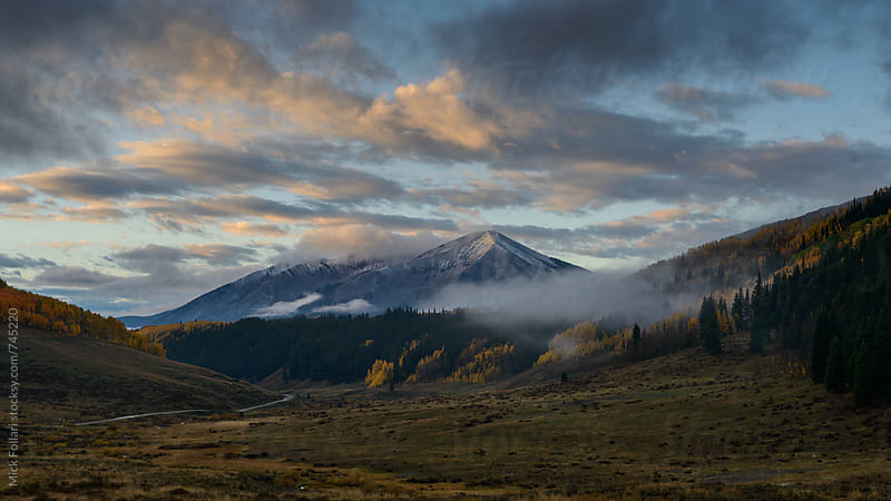Dramatic sky with autumn colors and mountains by Mick Follari for Stocksy United