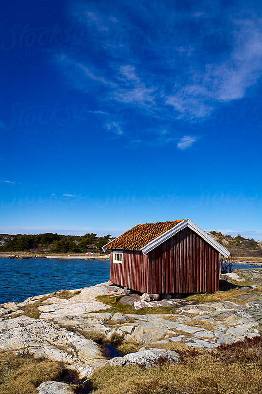 Red boat-house at the sea with a blue sky by Jonas Räfling for Stocksy United
