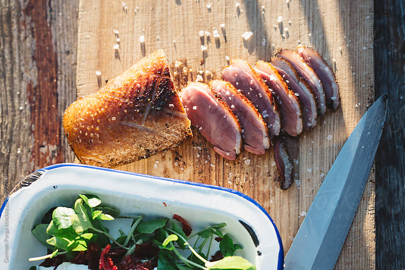 freshly smoked duck breast, cut into small pieces by German Parga for Stocksy United