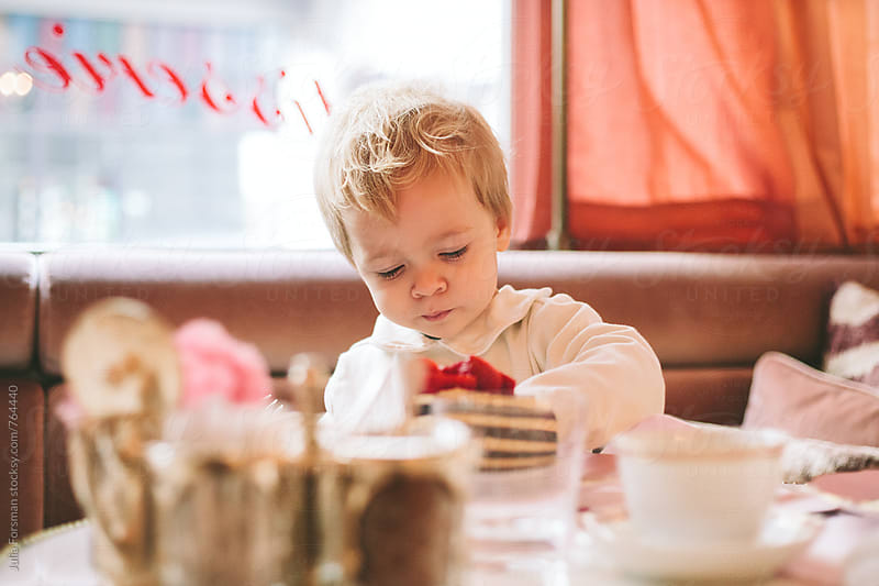 Little girl eats cake in a pretty café. by Julia Forsman for Stocksy United