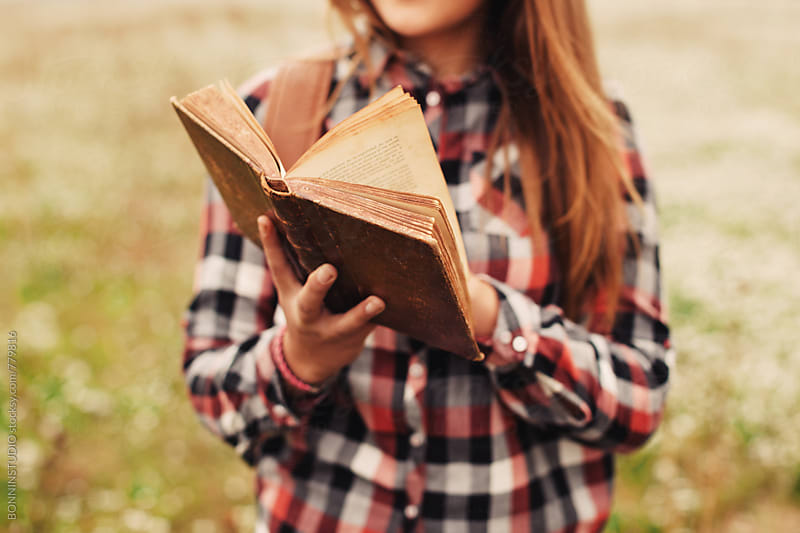 Closeup of a 14 years old girl reading an old book in a rural landscape. by BONNINSTUDIO for Stocksy United