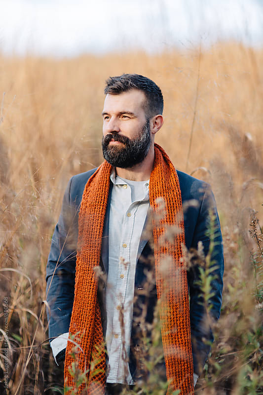 Handsome man with a beard standing in a field of tall grass by Jakob for Stocksy United