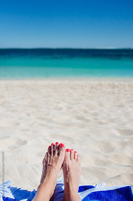 Relaxing on the beach beside the clear blue water of the Indian Ocean by Angela Lumsden for Stocksy United