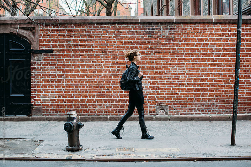 Young woman in black walking down the street by michela ravasio for Stocksy United