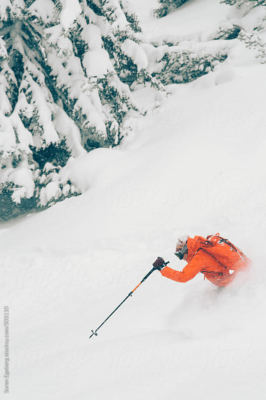 Happy girl having fun skiing deep powder snow in the forest of the winter mountains by Soren Egeberg for Stocksy United