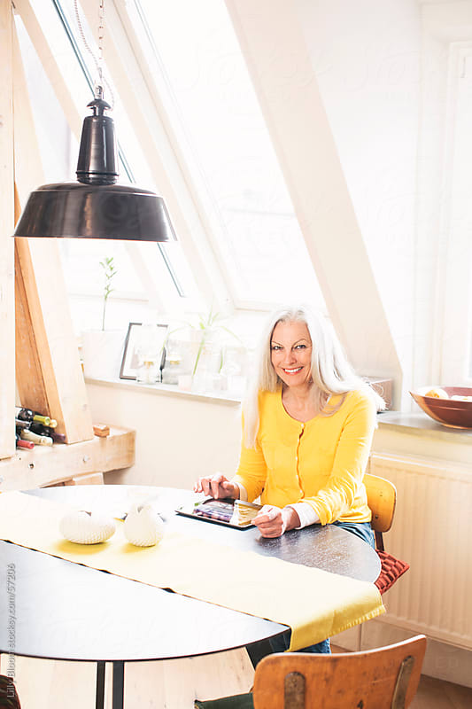 Portrait of a beautiful senior woman in a modern loft, using a tablet pc. by Lilly Bloom for Stocksy United