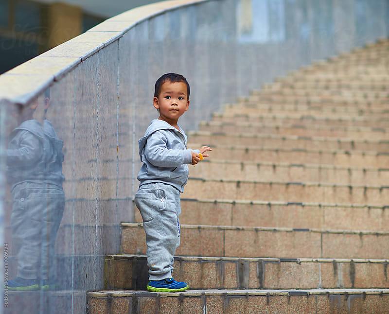 lovely little boy on steps by Bo Bo for Stocksy United